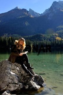 Junge Frau liest an einem Bergsee