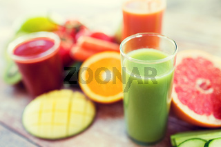 close up of fresh juice glass and fruits on table