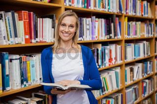 Happy female student reading a book in the library
