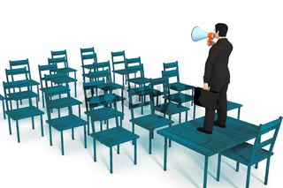 Businessman with megaphone speaking to empty chairs