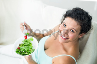 Portrait of happy woman eating salad
