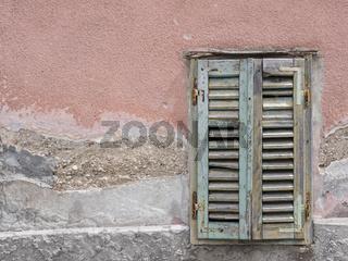 Grüner Fensterladen in der Fassade eines alten Gebäudes