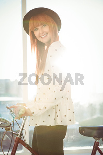Smiling hipster woman with her bicycle