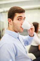 Junger Geschäftsmann trinkt eine Tasse Kaffee