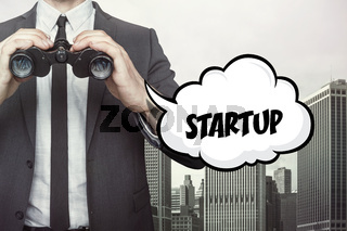 Startup text on speech bubble with businessman holding binoculars