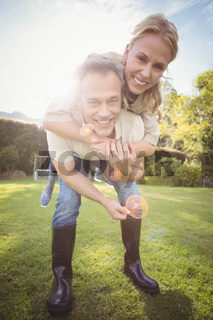 Husband giving piggy back to wife