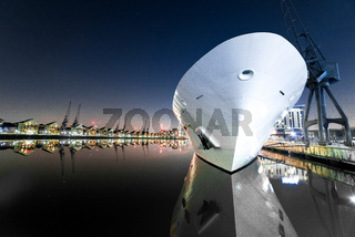 Ship and cranes with reflections, Royal Victoria Dock at night, Docklands, London, United Kingdom