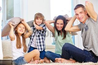 Familie und Kinder machen Kissenschlacht