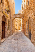 Narrow street among old stone walls of Jewish Quarter in Jerusalem, Israel.