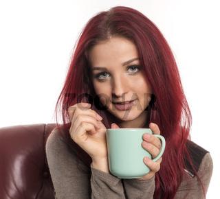 frau mit roten haaren hält eine kaffeetasse