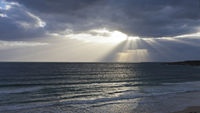 Moody Sky above the wide great sea with powerful sunbeams breaking through the cloudscape