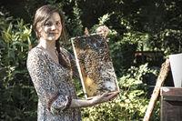 Imkerin arbeitet am Bienenstand