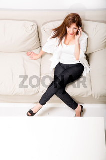 A beautiful mature woman talking on her cell phone on the sofa