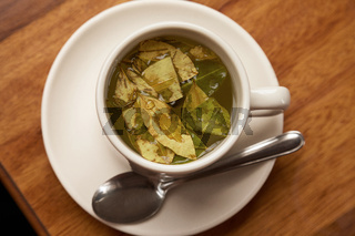 Cup of Coca Tea on Wooden table.