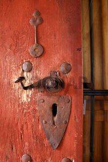 Alte Holztüre mit schweren Beschlägen und Klinke