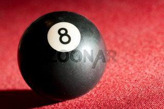 Billards pool or snooker game. The black eight ball. Red cloth table