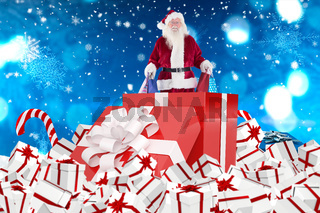 Composite image of santa standing in large gift