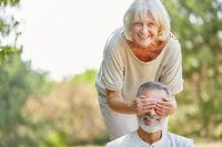 Seniorin hält ihrem Mann die Augen zu
