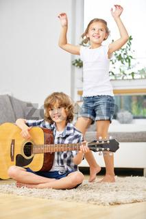 Mädchen tanzt und Junge spielt Musik auf Gitarre