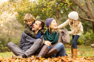 Smiling young family sitting in leaves