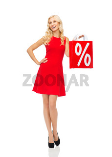 smiling woman in red dress with shopping bag
