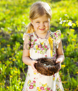 Little girl holding an Easter eggs in the nest