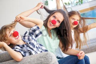 Mutter und Kinder im Karneval mit roten Nasen