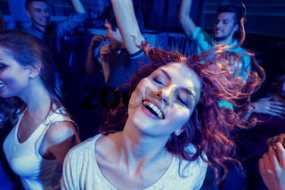 smiling friends dancing in club