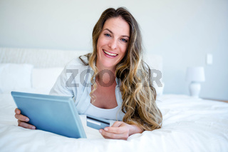 woman lying on her tablet holding her credit card