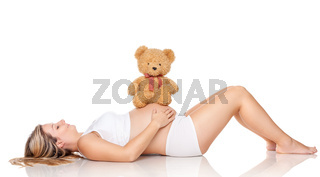 Cute teddy bear sitting on a belly of a pregnant woman
