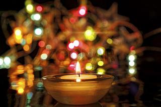 brennende Kerze und viele bunte Lichter