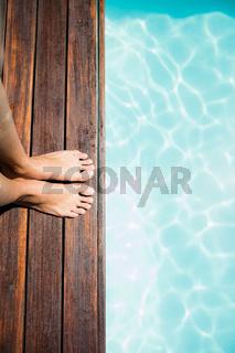 Woman feet on pools edge