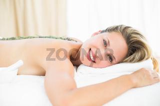 Beautiful blonde lying on massage table with lavanda