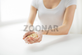 close up of woman hands holding oatmeal flakes