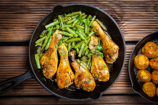 Chicken legs in pan with potatoes