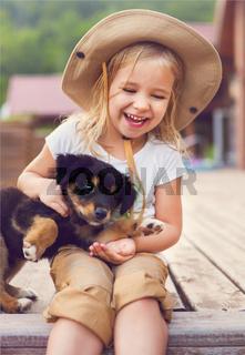 Cute little girl hugging dog puppy