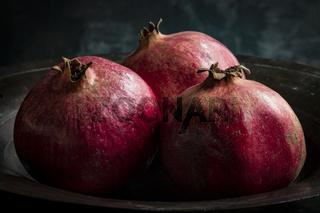 Stilleben mit drei Granatäpfeln in einer Kupferschale