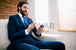 Businessman texting on the couch