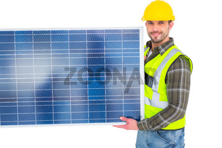Handyman in protective clothing carrying solar panel