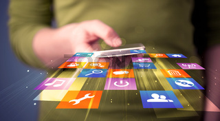 Woman holding smart phone with colorful application icons