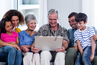 Happy family using laptop on sofa