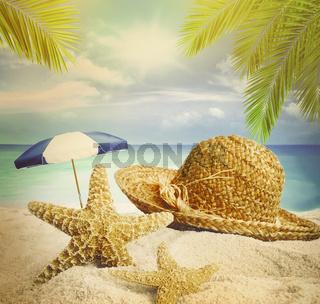 Sandy beach, straw hat and starfish in summer