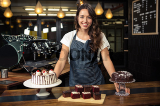 Smiling barista presenting plate with cakes