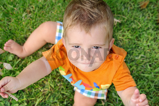 blond baby sitting on grass with a twig in his hand