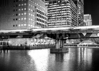 DLR Train Passing over bridge in black and white, Canary Wharf, London, United Kingdom