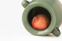 A pomegranate inside the greenish earthen jar
