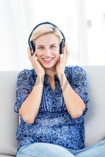 Pretty blonde woman listening music on the couch