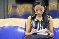 woman sitting in the subway car and writes notes