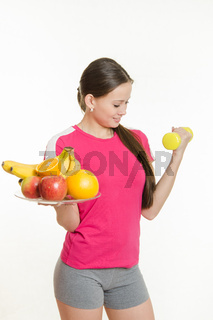 Athlete swings his left hand holding a plate of fruit in his right hand