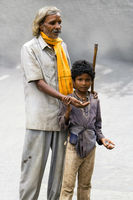 A blind man begging for money with the help of a young boy - India